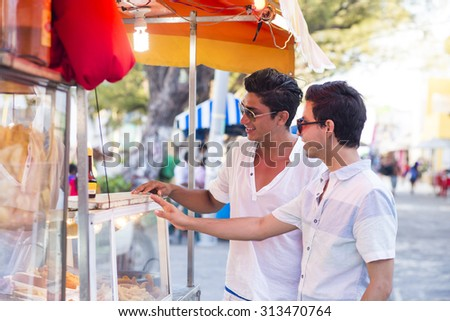 Couple traveling in latin america, buying street food in a truck. Isla Mujeres, Mexico. - stock photo