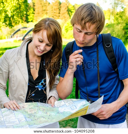 Couple traveling, they look at a map - stock photo