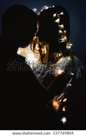 Couple. Two lovers in dark. Girl entwined with lights. The wedding night