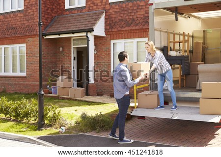 Couple Unpacking Moving In Boxes From Removal Truck - stock photo