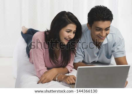 Couple using a laptop on the bed