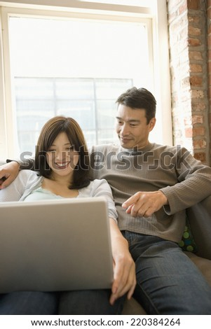Couple using a laptop together - stock photo