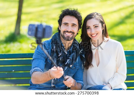 Couple using a selfie stick - stock photo