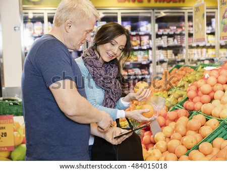 Couple Using Digital Tablet While Choosing Oranges