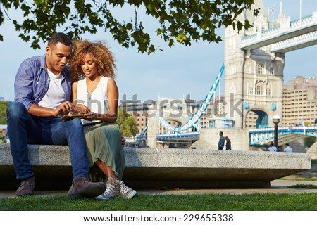 Couple Using Digital Tablet With Tower Bridge In Background - stock photo