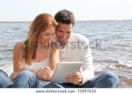 Couple using electronic tablet by a lake - stock photo