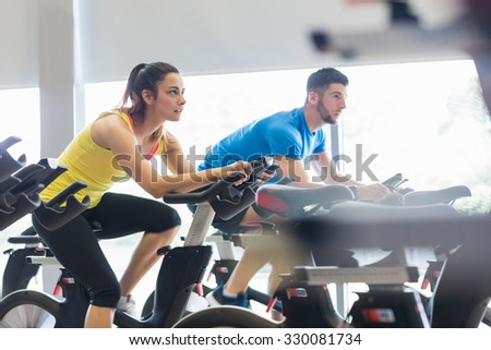 Couple using exercise bikes together at the gym