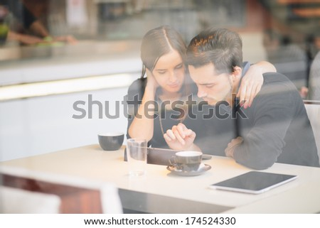 Couple using tablet computer in cafe - stock photo