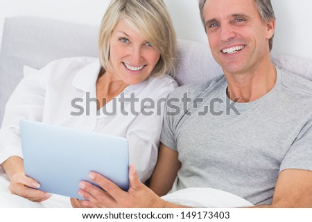Couple using tablet pc in bed smiling at camera at home in bedroom