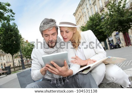 Couple visiting city with help of map and electronic tablet - stock photo