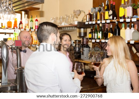 couple waiting for table in restaurant and drinking wine at tavern. Focus on the woman - stock photo