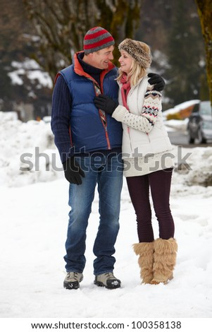 Couple Walking Along Snowy Street In Ski Resort - stock photo