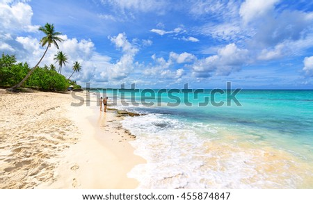 Couple walking along the tropical coast of the Dominican Republic. Tropical beach.