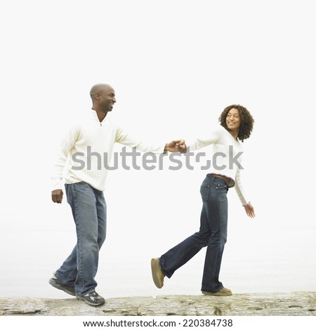 Couple walking and holding hands - stock photo