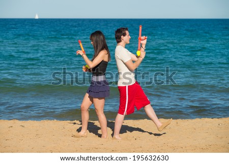 Couple walking away from each other to start a water gun duel - stock photo