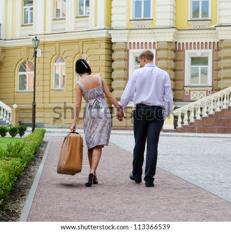 Couple walking away from the camera hand in hand with the woman leaning sideways due to the weight of the luggage she is carrying