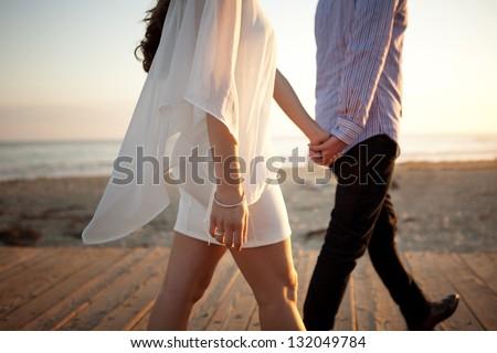 Couple Walking Away on Beach - stock photo