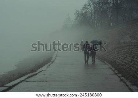 Couple walking beside river on misty winter day. - stock photo