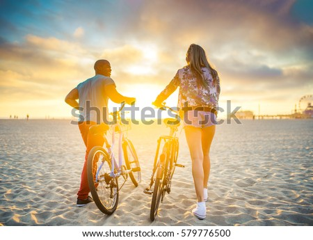 couple walking bikes together on beach to stunning sunset with lens flare