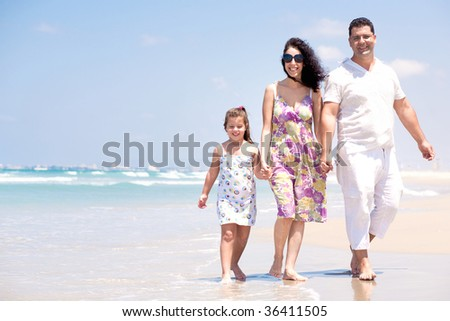 Couple walking by the sea along with daughter - stock photo