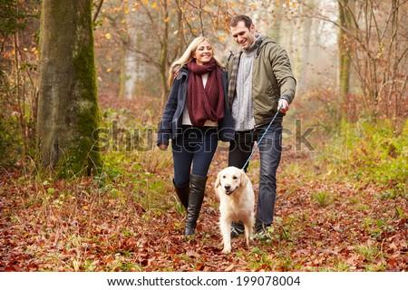 Couple Walking Dog Through Winter Woodland - stock photo
