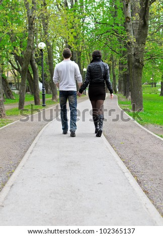 Couple walking down the road in the park. From the back