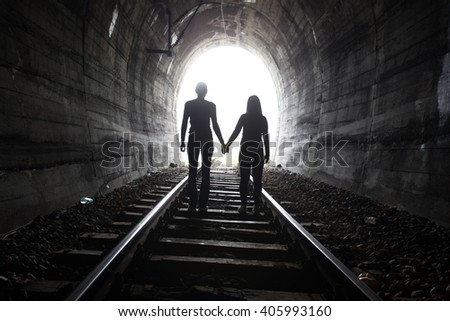 Couple walking hand in hand along the track through a railway tunnel towards the bright light at the other end, they appear as silhouettes against the light - stock photo