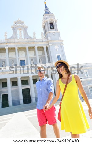 Couple walking holding hands in Madrid, Spain in front of landmark and tourist attraction Almudena Cathedral. - stock photo