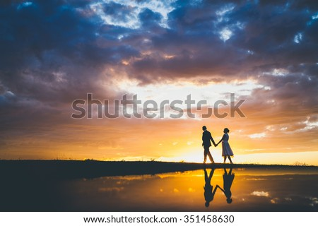 Couple walking in the sunset - stock photo