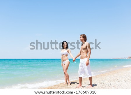 Couple walking on beach, love hold hands. Young happy man and woman walk sea shore smiling romantic looking each other, summer ocean vacation holiday blue sky
