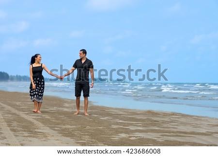 Couple walking on beach.Young happy interracial couple walking on beach  and smiling to each other. Asian woman,Caucasian man   - stock photo