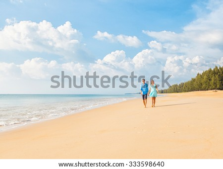 Couple walking on beach. Young happy interracial couple walking on beach smiling holding around each other. - stock photo