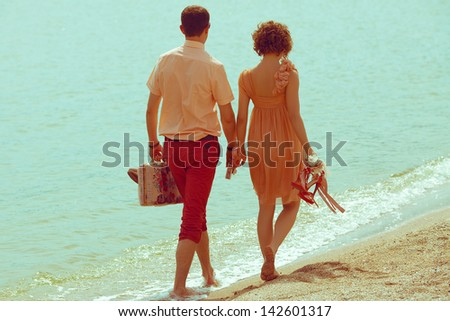 Couple walking on beach. Young happy married couple walking on beach holding around each other and holding their shoes. Sunny summer day. Outdoor shot