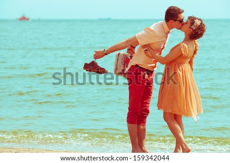 Couple walking on beach. Young happy married hipsters in trendy clothes kissing on beach and holding their shoes. Sunny summer day. Copy-space. Outdoor shot