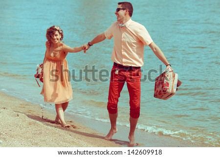 Couple walking on beach. Young happy married hipsters in trendy clothes playing and laughing on beach and holding their shoes. Sunny summer day. Outdoor shot