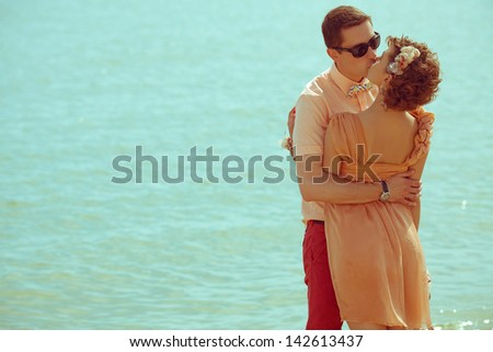 Couple walking on beach. Young happy married hipsters in trendy clothes standing and kissing on beach. Sunny summer day. Copy-space. Vintage style. Outdoor shot