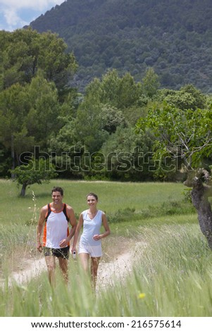 Couple walking on path through rural field - stock photo