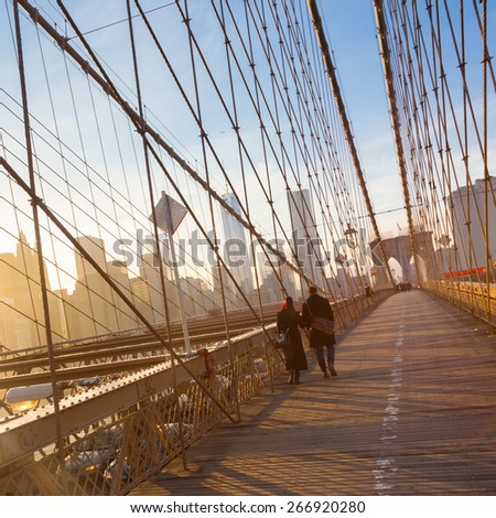 Couple walking on pedestrian path across Brooklyn bridge. New York City Manhattan downtown skyline in sunset with skyscrapers illuminated over East River panorama as seen from Brooklyn bridge. - stock photo