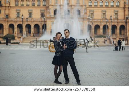 Couple walking on Plaza de Espana Seville a popular tourist destination landmark. Romantic couple visiting Spanish tourists attractions sightseeing in Seville, Spain. - stock photo