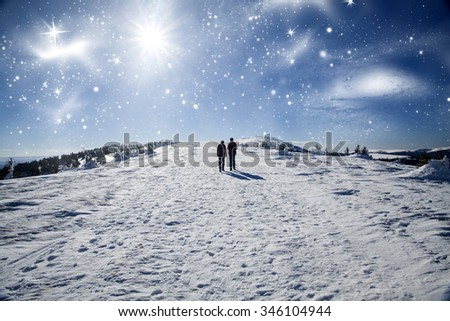 Couple walking on snow trail in winter mountains