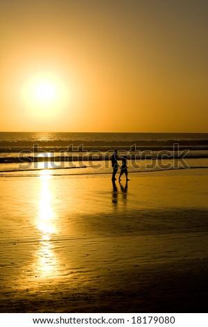 Couple walking on the beach at sunset. - stock photo