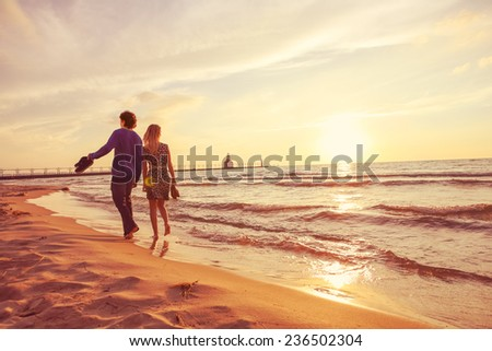 Couple walking on the beach at sunset - stock photo