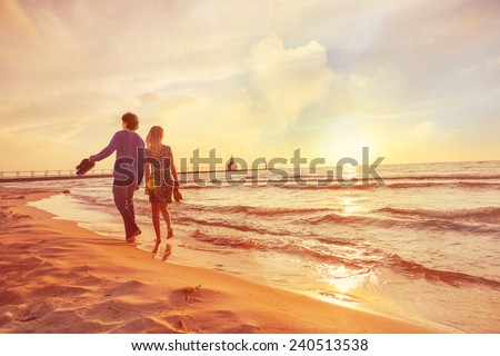 Couple walking on the beach at sunset. Heart shaped cloud in sky. Instagram filter - stock photo