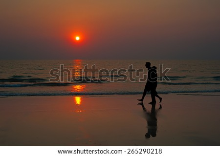 Couple walking on the beach at sunset. Thailand