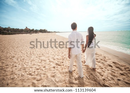 Couple walking on the beach holding hands - stock photo