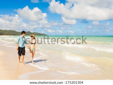 Couple walking on the beach. Young happy interracial couple walking on beach holding hands. - stock photo