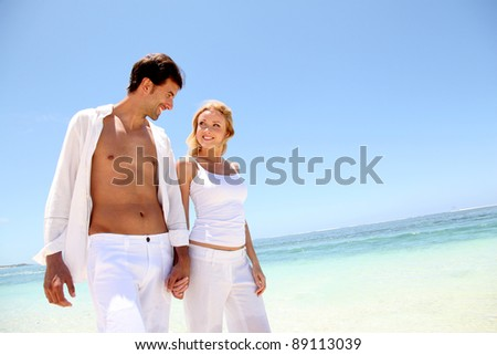 Couple walking on white sandy beach - stock photo