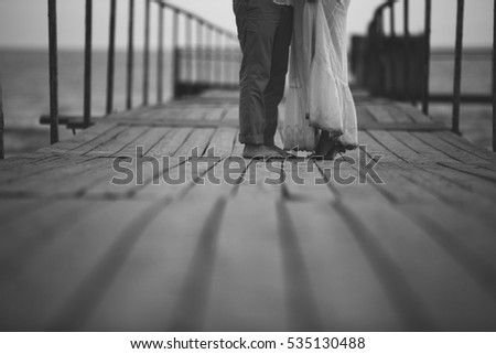 Couple walking seaside beach, love story concept near sea, holding each others hands, symbol of romance and love, white and black