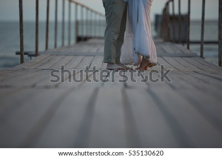 Couple walking seaside beach, love story concept near sea, holding each others hands, symbol of romance and love,