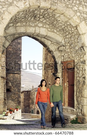 Couple walking through the gate of an italian village